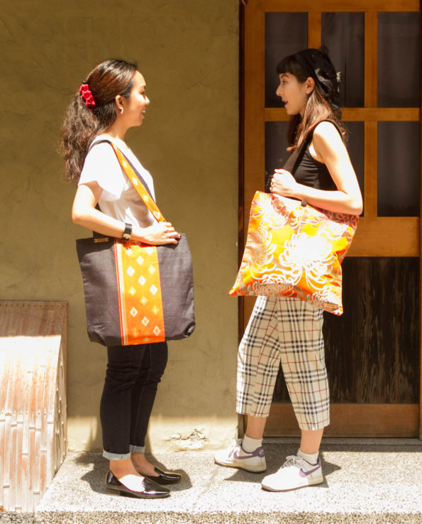 Two models standing in a doorway with large tote bags