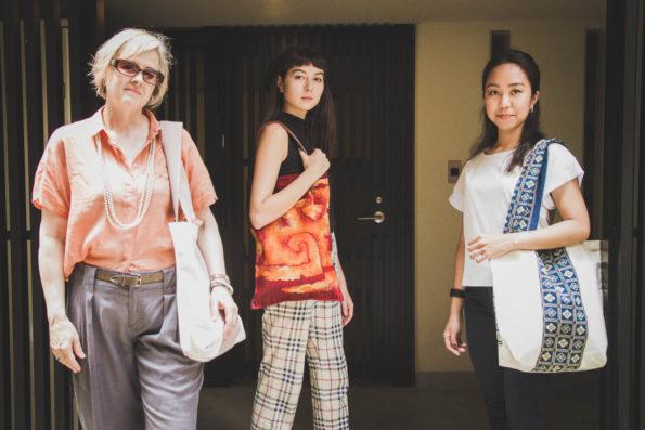 Models standing in a doorway modelling large tote bags